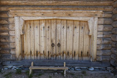 Beautiful old door on the wooden wall of the old house. Excellent background. Stock Image