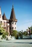 Beautiful old fairy-tale castle.  Walls of the castle, green flower garden. Stone walkway. Alley in beautiful Royalty Free Stock Photo