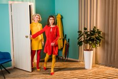 Beautiful old-fashioned girls in colorful dresses entering apartment. At home royalty free stock photography