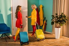 Beautiful old-fashioned girls in colorful dresses with travel bags opening door. At home royalty free stock photography