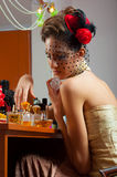 Beautiful old fashioned lady plays with perfumes Stock Image