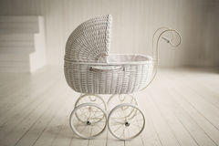 Beautiful old fashioned white pram in white room Stock Images