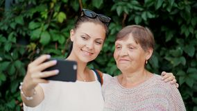 Beautiful old granny and her granddaughter doing selfie outdoor on foliage background, looking at camera and smiling to. Smartphone camera. Technology, memory stock video