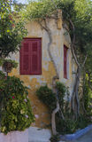 Beautiful old house with red shutters, surrounded by green bushe Stock Photos