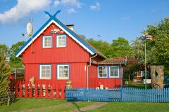 Red wooden house. Beautiful old Lithuanian traditional wooden red house  with garden in Nida, Lithuania, Europe royalty free stock images
