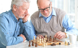 Beautiful old men play chess. At the table Royalty Free Stock Photography
