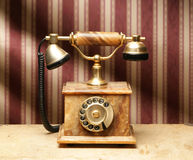 A beautiful old phone on a vintage background. A beautiful old phone on a desk. The image is taken in a studio on a vintage background Royalty Free Stock Photography