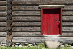 Beautiful old red door on the wooden wall of the old house. Excellent background. Royalty Free Stock Photo