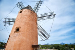 Beautiful old spain windmill against colorful sky with clouds. Spring landscape in the morning in Paguera. Rural scene Royalty Free Stock Image