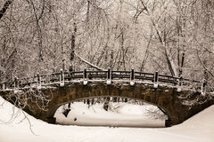 Beautiful old stone bridge of  winter forest in the snow at sunset frosty days. Trees covered in frost and snow. Royalty Free Stock Images