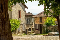 Beautiful old stone houses in Perouges, France. Typical facade of the old Provencal stone house with wooden doors decorated with colorful geranium spots in royalty free stock image