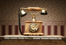 A beautiful old vintage phone standing on a table. A beautiful old vintage brown telephone standing on a table. The image is taken on a vintage background Stock Photos