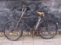Beautiful old, vintage and retro bicycle, dating from 1950`s parked in the passage between old houses secured with chain. Natural. Ambient sunlight stock image