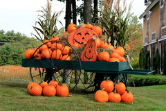Beautiful old wagon with bright,colorful pumpkins and Jack-o-lanterns Royalty Free Stock Images