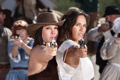 Beautiful Old West Women with Guns. Pretty female gunfighters with pistols at point blank range Stock Photography