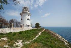 Beautiful old white lighthouse on the sea coastline. Summer seascape Stock Photos