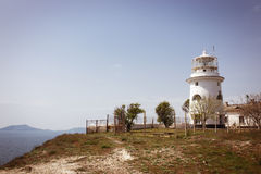 Beautiful old white lighthouse on the sea coastline. Summer seascape. Royalty Free Stock Images