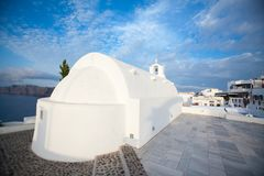 White architecture on Santorini island, Greece. Beautiful old white ortodox church in sunny day with blue sky in Oia on Santorini island. Santorini is romantic Royalty Free Stock Images