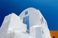 Beautiful old white ortodox church in sunny day with blue sky in Oia on Santorini island. Santorini is romantic place Stock Photo