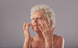 Beautiful old woman applying moisturizer on her face. Portrait of beautiful old woman applying moisturizer on her face against grey background. Senior woman Stock Photography