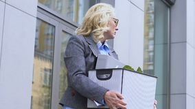 Beautiful old woman holding cardboard box, upset by dismissal, resignation. Stock footage stock video