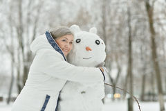 Beautiful old woman. Portrait of a beautiful old woman with snowman in the winter Stock Photo