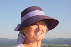 Beautiful old woman. With a purple hat enjoying the sun stock images