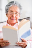 Beautiful old woman reading a book Stock Photos
