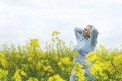 Beautiful old woman in yellow field Royalty Free Stock Photo