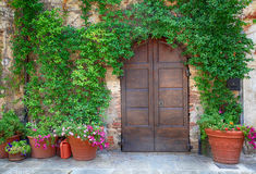 Beautiful old wooden door decorated with flowers, Italy. Beautiful old wooden door decorated with flowers from the medieval town, Tuscany, Italy Royalty Free Stock Photo