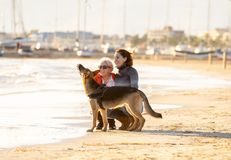 Beautiful older mom and mature daughter walking their german shepard dog on beach at autumn sunset stock image