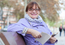 Beautiful older woman  on bench Royalty Free Stock Photo