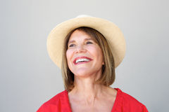 Beautiful older woman laughing with hat against gray wall Royalty Free Stock Image