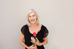 Beautiful older woman laughing with red rose in black blouse Royalty Free Stock Photography