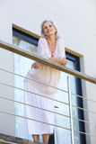Beautiful older woman leaning on terrace railing smiling Stock Photography