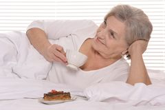 Beautiful older woman resting in the bedroom Stock Image