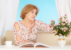 Beautiful older woman resting in the bedroom Stock Photo