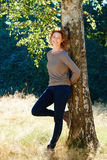 Beautiful older woman smiling leaning against tree. Portrait of beautiful older woman smiling leaning against tree royalty free stock image