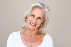 Beautiful older woman smiling and standing by wall Stock Image