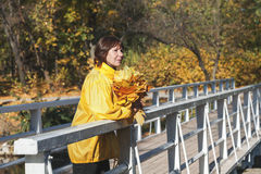 Beautiful older woman standing on bridge with bunch of leaves Stock Photography
