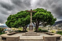 Barcelos Funchal monument. Beautiful ominous view of the monument cross on top of the Barcelos viewpoint Miradouro Pico dos Barcelos in Funchal, Madeira royalty free stock photography
