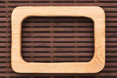 Beautiful one-piece wooden frame, lies on bamboo mat. Natural patterns royalty free stock images