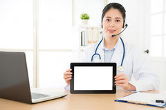 Beautiful online doctor showing tablet computer Royalty Free Stock Photos