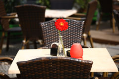 Beautiful open air summer restaurant tables with red flower in vase. Beautiful open air summer restaurant tables and chairs served with red flower in vase Royalty Free Stock Photo