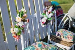 Beautiful open terrace in the garden with tiffany coloured vintage white chairs, colorful velvet pillow and fence palisade, bicycl Stock Image