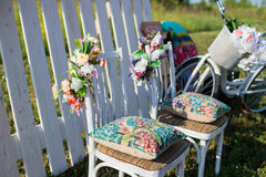 Beautiful open terrace in the garden with tiffany coloured vintage white chairs, colorful velvet pillow and fence palisade, bicycl Stock Images
