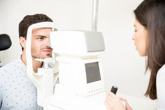 Young optometrist with autorefractor checking man patient at eye stock image