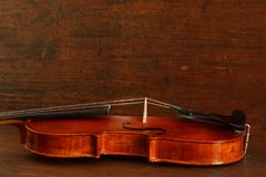 Beautiful antique violin on brown wood background royalty free stock photo