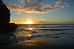 Sunset at piha beach in New Zealand. Beautiful orange color sunset at piha beach in New Zealand stock photography