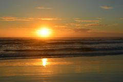 Sunset at piha beach in New Zealand. Beautiful orange color sunset at piha beach in New Zealand royalty free stock photos